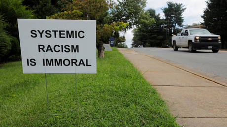 FILE PHOTO: A sign against racism is seen outside a church in Charlottesville, Virginia.