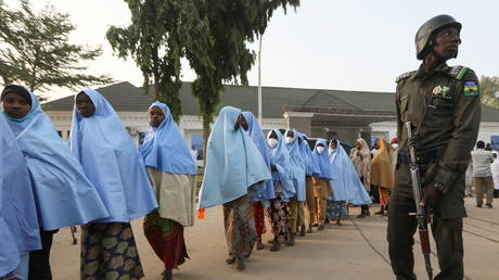 Girls who were kidnapped from a boarding school in the northwest Nigerian state of Zamfara, walk in line after their release, as a police officer stands close in Zamfara, Nigeria March 2, 2021 © REUTERS/Afolabi Sotunde