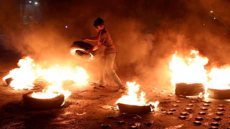 A demonstrator stands near burning tires in Beirut, Lebanon, March 2, 2021