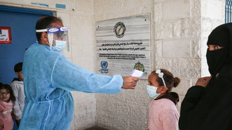 An health worker measures the temperature of a girl in Rafah, Gaza Strip, on March 3, 2021.