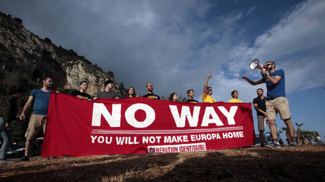"""Banned far right demonstrators from """"Generation Identitaires"""" hold a banner which reads, """"No Way - You will not make Europa home"""" (FILE PHOTO) ©  REUTERS/Eric Gaillard"""