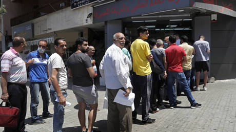 FILE PHOTO: People line up outside an exchange shop to buy US dollars, in Beirut, Lebanon, June 17, 2020.