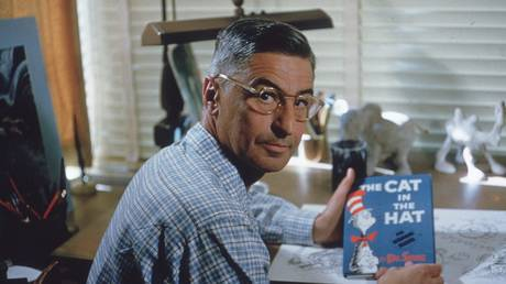 American author and illustrator Dr Seuss (Theodor Seuss Geisel, 1904 - 1991) sits at his drafting table in his home office with a copy of his book, 'The Cat in the Hat', La Jolla, California, April 25, 1957.