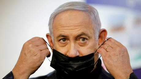 FILE PHOTO: Israeli Prime Minister Benjamin Netanyahu adjusts his protective face mask after receiving a coronavirus disease (COVID-19) vaccine at Sheba Medical Center in Ramat Gan, Israel December 19, 2020