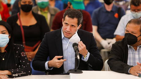 Venezuelan opposition leader Juan Guaido removes his face mask while arriving to a news conference in Caracas, Venezuela March 3, 2021.