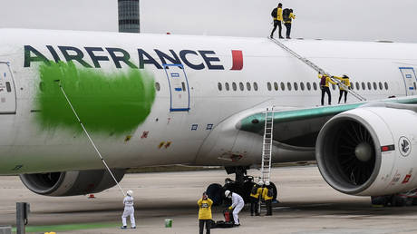 Members of Greenpeace painting an Air France passenger aircraft parked on the tarmac at the Roissy-Charles de Gaulle International airport (CDG), north of Paris on March 5, 2021.