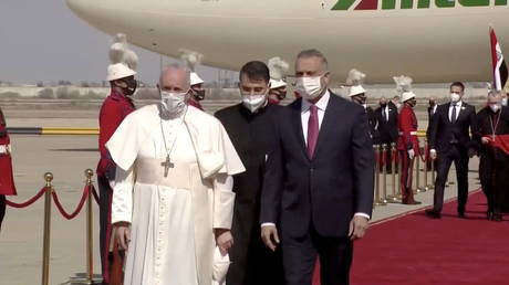 Iraqi Prime Minister Mustafa Al-Kadhimi welcomes Pope Francis as he arrives at Baghdad International Airport to start his historic tour in Baghdad, Iraq, March 5, 2021, in this screen grab taken from video.