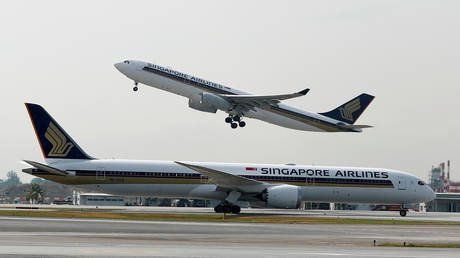FILE PHOTO: FILE PHOTO: A Singapore Airlines Airbus A330-300 plane takes off behind a Boeing 787-10 Dreamliner at Changi Airport in Singapore March 28, 2018.