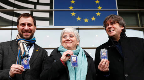 Former members of the Catalan government Toni Comin, Clara Ponsati and Carles Puigdemont show their badges outside the European Parliament in Brussels, Belgium February 5, 2020. © Reuters / Francois Lenoir