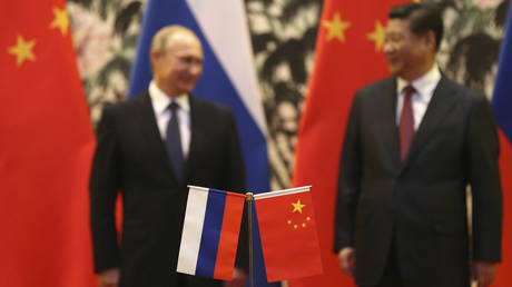 Russian and Chinese national flags are seen on the table with Russian President Vladimir Putin (L) and his Chinese counterpart Xi Jinping stand in the background during a signing ceremony at the Diaoyutai State Guesthouse in Beijing, November 9, 2014.  © Reuters / How Hwee Yong