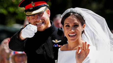 FILE PHOTO: Britain's Prince Harry gestures next to his wife Meghan as they ride a horse-drawn carriage after their wedding ceremony at St George's Chapel in Windsor Castle in Windsor, Britain, May 19, 2018 © REUTERS/Damir Sagolj