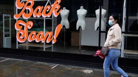 A woman walks past a closed retail unit amid the outbreak of the coronavirus disease in Manchester, Britain, March 8, 2021 © REUTERS/Phil Noble