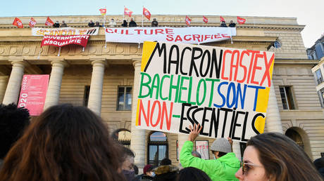 FILE PHOTO: A French activist holds a placard reading 'Macron, Castex, Bachelot, are non-essential' at the French Theatre Odeon theatre de l'Europe, in Paris, on March 6, 2021 © AFP / BERTRAND GUAY
