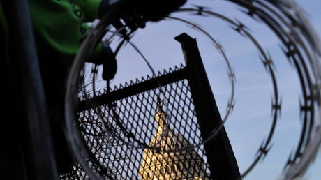 FILE PHOTO: Workers install razor wire atop a security barrier surrounding the US Capitol, in Washington, DC, January 14, 2021.