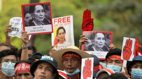 Demonstrators hold placards with pictures of Aung San Suu Kyi as they protest against the military coup in Yangon, Myanmar, (FILE PHOTO) © REUTERS/Stringer