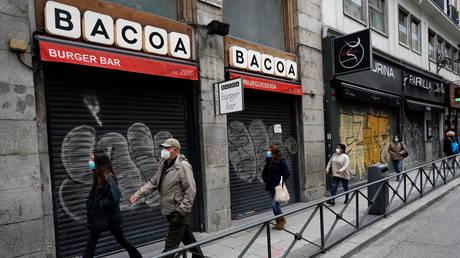People walk near closed shops amid the coronavirus disease outbreak in Madrid, Spain