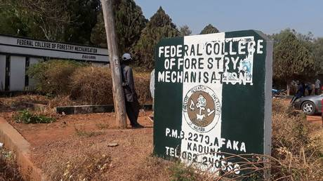 A man rests on a pole beside the signage of the Federal College of Forestry Mechanization where gunmen abducted students, in Kaduna, Nigeria March 12, 2021.