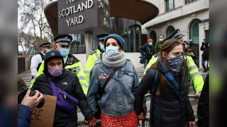 Protesters are shown locking hands in front of police on Sunday at New Scotland Yard in London.