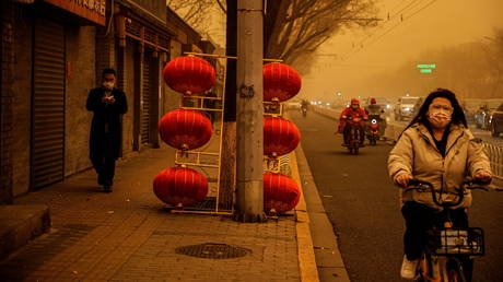 People go about their day during morning rush hour as Beijing, China, is hit by a sandstorm, March 15, 2021.