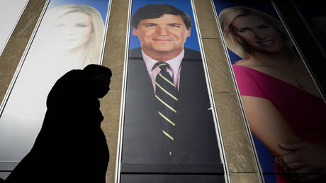 FILE PHOTO: People pass by a promo of Fox News host Tucker Carlson on the News Corporation building in New York, U.S., March 13, 2019