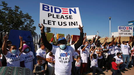 FILE PHOTO: Migrants from Central America and other nationalities, hoping to cross and request asylum in the US, hold banners and shout slogans to US President Joe Biden at their campsite outside El Chaparral border crossing, in Tijuana, Mexico February 27, 2021