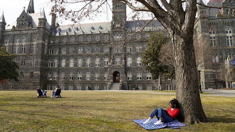 Masked to protect against the coronavirus disease (COVID-19), Georgetown University student takes advantage of the warm sunshine to study outdoors in Washington, US, March 9, 2021