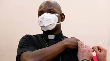 FILE PHOTO: Father Hilaire Belizaire of the Sacred Heart Church in Queens, New York, receives his first dose of Pfizer's coronavirus vaccine in Valley Stream, New York.