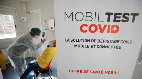 """A medical worker administers a nasal swab to a patient at a COVID-19 mobile test centre called """"MobilTest COVID"""" France (FILE PHOTO) © REUTERS/Eric Gaillard"""