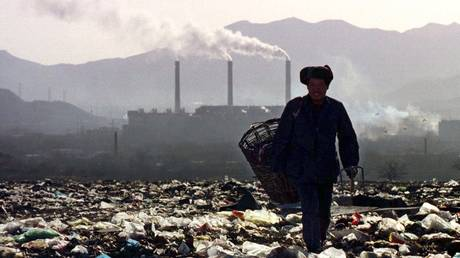 """FILE PHOTO. A scavenger takes a stroll with a rattan basket on a vast rubbish dump in a Beijing suburb. Perched among the western """"Fragrant Hills"""" near a smoke-belching steel factory. © Reuters / RPA for RNPS AYCE customers, Reuters Pictures Archive"""