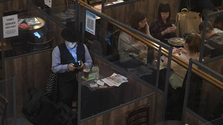 A customer sits at a table which is separated by Perspex screens as part of social distancing measures at a pub in the Soho district of London on October 18, 2020 © AFP / JUSTIN TALLIS