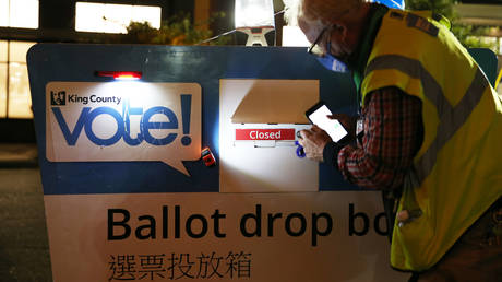 FILE PHOTO: King County Elections worker Jules James closes the ballot drop box at the Seattle Public Library - Ballard branch on November 3, 2020 in Seattle, Washington
