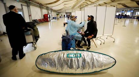 A passenger gets tested for coronavirus after arriving on a flight to Israel at Ben Gurion international airport near Tel Aviv. © Reuters / Amir Cohen