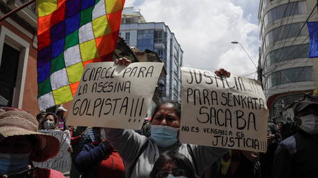 """A demonstrator during a protest in front of the FELCC headquarters to demand jail for former interim President Jeanine Anez in La Paz, Bolivia, March 14, 2021. Placards read: """"Jail for the murderer coup plotter"""" and """"Justice for Senkata Sacaba. It's not vengeance, it's justice"""""""