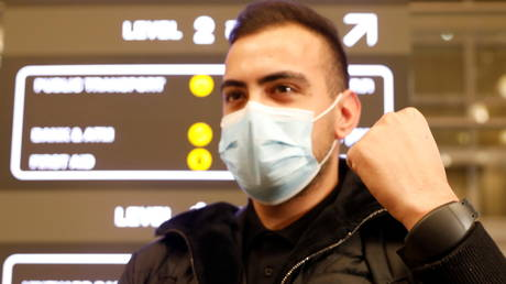 A man wears an electronic tracking bracelet used to enforce coronavirus quarantines in Israel, at the Ben Gurion international airport near Tel Aviv, Israel, March 1, 2021.