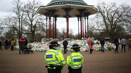 Police officers stand next to a memorial site at the Clapham Common Bandstand, following the kidnap and murder of Sarah Everard, in London, Britain March 16, 2021. © Reuters / Hannah McKay