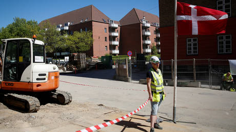 """FILE PHOTO: A worker stands beside a Danish flag on a construction site of new housing being built next to Mjolnerparken, a housing estate that features on the Danish government's """"Ghetto List"""", in Copenhagen, Denmark, May 8, 2018"""