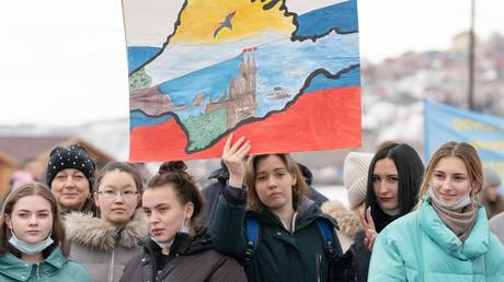 A young woman holds a drawing of the Swallow's Nest castle (Lastochkino gnezdo) as she takes part in a rally marking the seventh anniversary of the referendum on the state status of Crimea and Sevastopol and its reunification with Russia, in Petropavlovsk-Kamchatsky, Russia.
