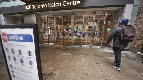 A man arrives at the entrance to the Toronto Eaton Centre in downtown Toronto, Ontario on November 23, 2020, the first day of a new lockdown in the city.
