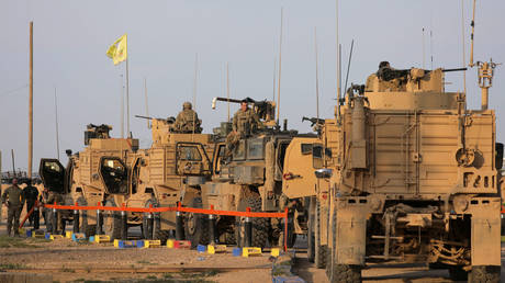 FILE PHOTO: American soldiers stand near military trucks, at al-Omar oil field in Deir ez-Zor, Syria, March 23, 2019.