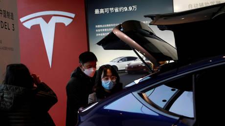 Visitors check a Tesla vehicle at a showroom in Beijing, China, January 2021. © Tingshu Wang / Reuters