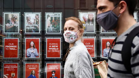 People wearing protective face masks walk past the window display of a travel agent in London, Britain, March 21, 2021 © Reuters / Henry Nicholls
