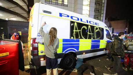 A demonstrator graffitis a police vehicle during a protest in Bristol, Britain, (FILE PHOTO) © REUTERS/Peter Cziborra