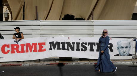 """A woman walks past a banner depicting Israeli PM Netanyahu and words """"Crime Minister"""" outside the Justice Ministry in Jerusalem"""