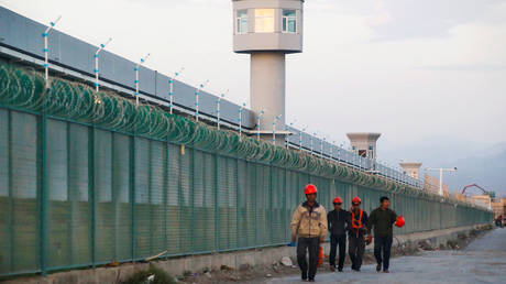Workers walk by the perimeter fence of what is officially known as a vocational skills education centre in Dabancheng in Xinjiang Uighur Autonomous Region, China (FILE PHOTO) © REUTERS/Thomas Peter/File Photo