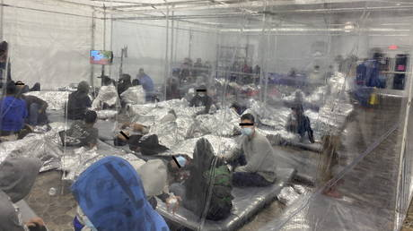 Migrants crowd a room with walls of plastic sheeting at the U.S. Customs and Border Protection temporary processing center in Donna, Texas, US in a recent photograph released March 22, 2021.