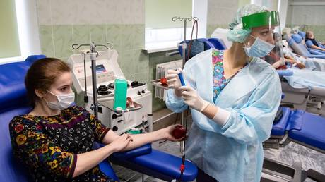 """A medic works with a patient vaccinated with Russian Gam-COVID-VAK (trademark """"Sputnik V"""") coronavirus vaccine who has come to donate antibody-rich plasma at the City Clinical Hospital No 52, in Moscow, Russia. © Sputnik"""