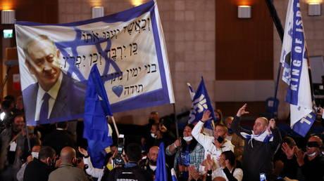 Supporters of Israeli PM Benjamin Netanyahu celebrate outside the Likud party headquarters in Jerusalem, March 24, 2021.