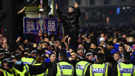 Police officers staff a cordon as Rangers football fans celebrate in George Square in central Glasgow on March 7, 2021 after their first Scottish Premiership title for 10 years was confirmed. © AFP / ANDY BUCHANAN