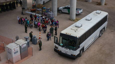 Asylum-seeking migrant families from Central America line up to be transported from a makeshift US Customs and Border Protection processing center, in Granjeno, Texas, March 24, 2021.