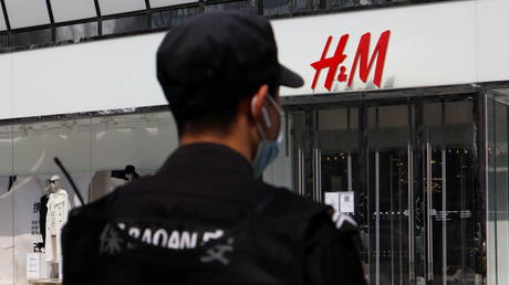A security guard stands outside a store of the Swedish fashion retailer H&M at a shopping complex in Beijing, China March 25, 2021. © REUTERS/Florence Lo